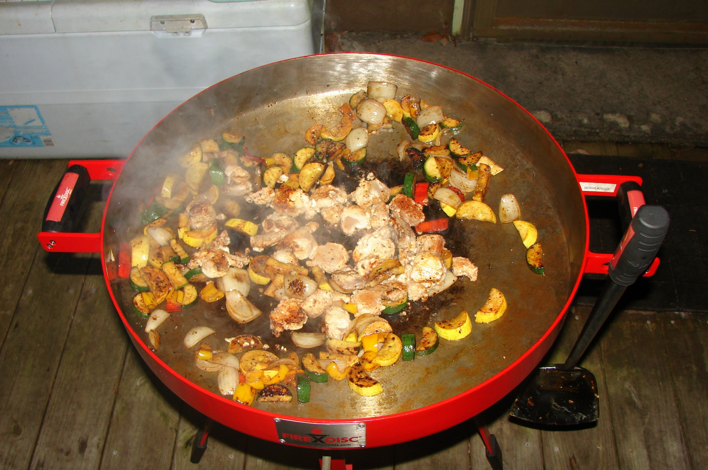 Chunks of wahoo fillets and vegetables sizzle in a FireDisc Cooker.
